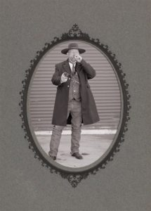 An old timey black and white photo of a man dressed like an old gunslinger